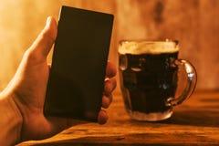 Mann mit dem mobilen und dunklen Bierkrug Lizenzfreie Stockfotografie
