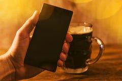 Mann mit dem mobilen und dunklen Bierkrug Lizenzfreies Stockfoto