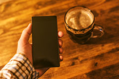 Mann mit dem mobilen und dunklen Bierkrug Stockbilder