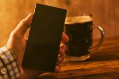 Mann mit dem mobilen und dunklen Bierkrug Stockfoto