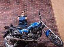 Mann mit dem Motorrad, das an der Backsteinmauer sich lehnt Stockfoto