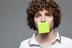 Mann mit dem Papier, das seinen Mund abdeckt Stockbild