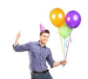 Mann mit dem Parteihut, der Ballone hält und Daumen aufgibt Stockfotografie