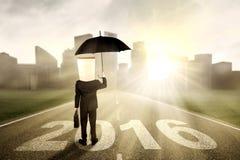Mann mit dem Regenschirm, der auf der Straße steht Stockbilder