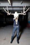 Mann mit dem Rotwildschädel im Keller Stockbild