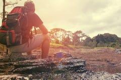 Mann mit dem Rucksack, der auf Felsen in wildem sitzt Lizenzfreies Stockfoto