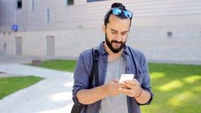 Mann mit dem Rucksack, der auf Smartphone in Stadt 30 simst stock video