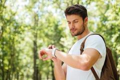 Mann mit dem Rucksack, der draußen Uhr steht und betrachtet Lizenzfreie Stockfotos