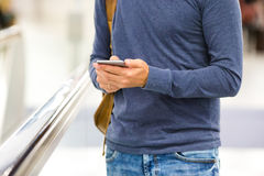 Mann mit dem Rucksack, der Handy am Flughafen hält lizenzfreies stockbild