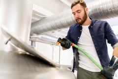 Mann mit dem Schlauch, der am Handwerksbier-Brauereikessel arbeitet Stockbilder