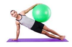 Mann mit dem Schweizer Ball, der Übungen tut Stockbild