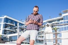 Mann mit dem skateboar Simsen auf smatphone stockbild