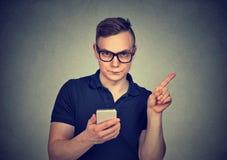 Mann mit dem Smartphonedarstellen keinem, Aufmerksamkeit mit Fingerhandzeichen Elterliches Bedienkonzept Stockfotos
