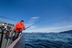 Mann mit dem Spinnen auf das Boot, das den Abstand untersucht Rotes Jac Stockbilder