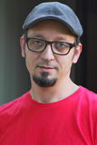 Mann mit dem Spitzbart, flacher Schutzkappe und Gläsern lizenzfreie stockfotos