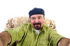 Mann mit dem Spitzbart im Lehnsessel, der selfie nimmt stockbild