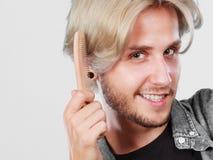 Mann mit dem stilvollen Haarschnitt, der sein Haar kämmt Stockfotografie