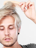 Mann mit dem stilvollen Haarschnitt, der sein Haar kämmt Lizenzfreies Stockbild