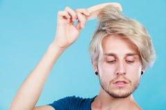 Mann mit dem stilvollen Haarschnitt, der sein Haar kämmt Stockbilder