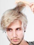 Mann mit dem stilvollen Haarschnitt, der sein Haar kämmt Lizenzfreie Stockfotografie