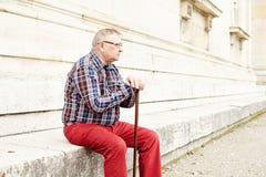 Mann mit dem Stocksitzen im Freien Lizenzfreie Stockbilder