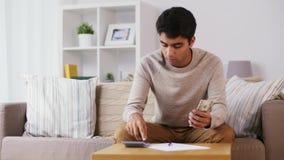 Mann mit dem Taschenrechner, der zu Hause Geld zählt stock footage