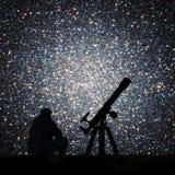 Mann mit dem Teleskop, das die Sterne betrachtet Kugelförmiger Block Stockbilder