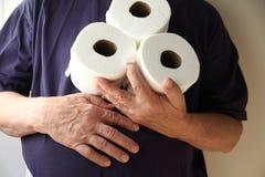 Mann mit dem unruhigen Magen hält Toilettenpapier stockfotos