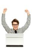 Mann mit den Armen angehoben unter Verwendung des Laptops Stockbild