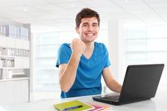 Mann mit den Armen angehoben unter Verwendung des Laptops Stockfotografie
