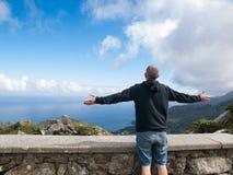 Mann mit den Armen streckte vor einer Küstenlandschaft aus Stockfotografie