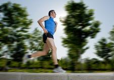 Mann mit den athletischen Beinen, die in Stadtpark mit Bäumen auf dem Hintergrund auf dem gesunden Lebensstil der Sommerschulungs Stockfoto