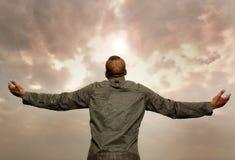 Mann mit den ausgestreckten Armen, die den Himmel betrachten Stockfotografie