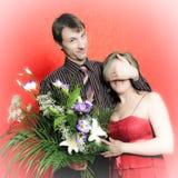 Mann mit den Blumen, die Augen der Frauen abdecken Stockfotografie