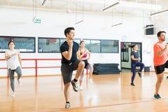 Mann mit den Freunden, die das hohe Knie läuft in der Aerobic-Klasse durchführen lizenzfreie stockbilder