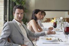 Mann mit den Freunden, die formales Abendessen haben Stockbilder