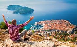 Mann mit den geöffneten Armen, die unten zur alten Stadt von Dubrovnik schauen Lizenzfreies Stockfoto
