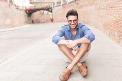 Mann mit den Gläsern, die auf dem Bürgersteig in einer Stadt sitzen Lizenzfreie Stockbilder