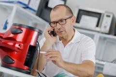Mann mit den Gläsern, die Gerät beim Anrufen reparieren stockfotos