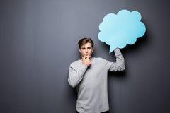 Mann mit den Händen auf dem Kinn, das blaue leere Spracheblase mit Raum für Text auf grauem Hintergrund hält Stockfotografie