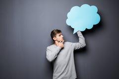 Mann mit den Händen auf dem Kinn, das blaue leere Spracheblase mit Raum für Text auf grauem Hintergrund hält Lizenzfreies Stockbild