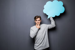 Mann mit den Händen auf dem Kinn, das blaue leere Spracheblase mit Raum für Text auf grauem Hintergrund hält Stockbilder