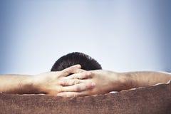 Mann mit den Händen hinter Kopf beim Fernsehen Stockbilder