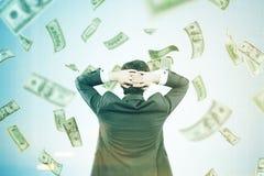 Mann mit den Händen hinter seinem Kopf in einem Geldstrom Stockbild