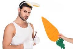 Mann mit den Häschenohren, die Tischbesteck während weibliche Hand dazu hält Karotte halten stockfotografie