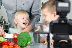 Mann mit den Kindern, welche die Mahlzeitvorbereitung filmen Heimvideo-Kamera, Blogging, kochend, inländische Küche Stockfoto