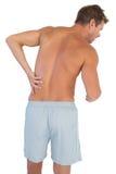 Mann mit den kurzen Hosen, die unter niedrigeren Rückenschmerzen leiden Lizenzfreies Stockbild