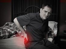 Mann mit den Rückenschmerzen, die auf Bett sitzen Stockbild