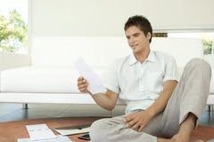 Mann mit den Rechnungen, die auf Fußboden sitzen Stockfoto