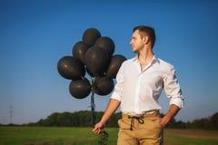 Mann mit den schwarzen Ballonen, die auf dem Gebiet und den Blicken in den Abstand stehen Stockbild